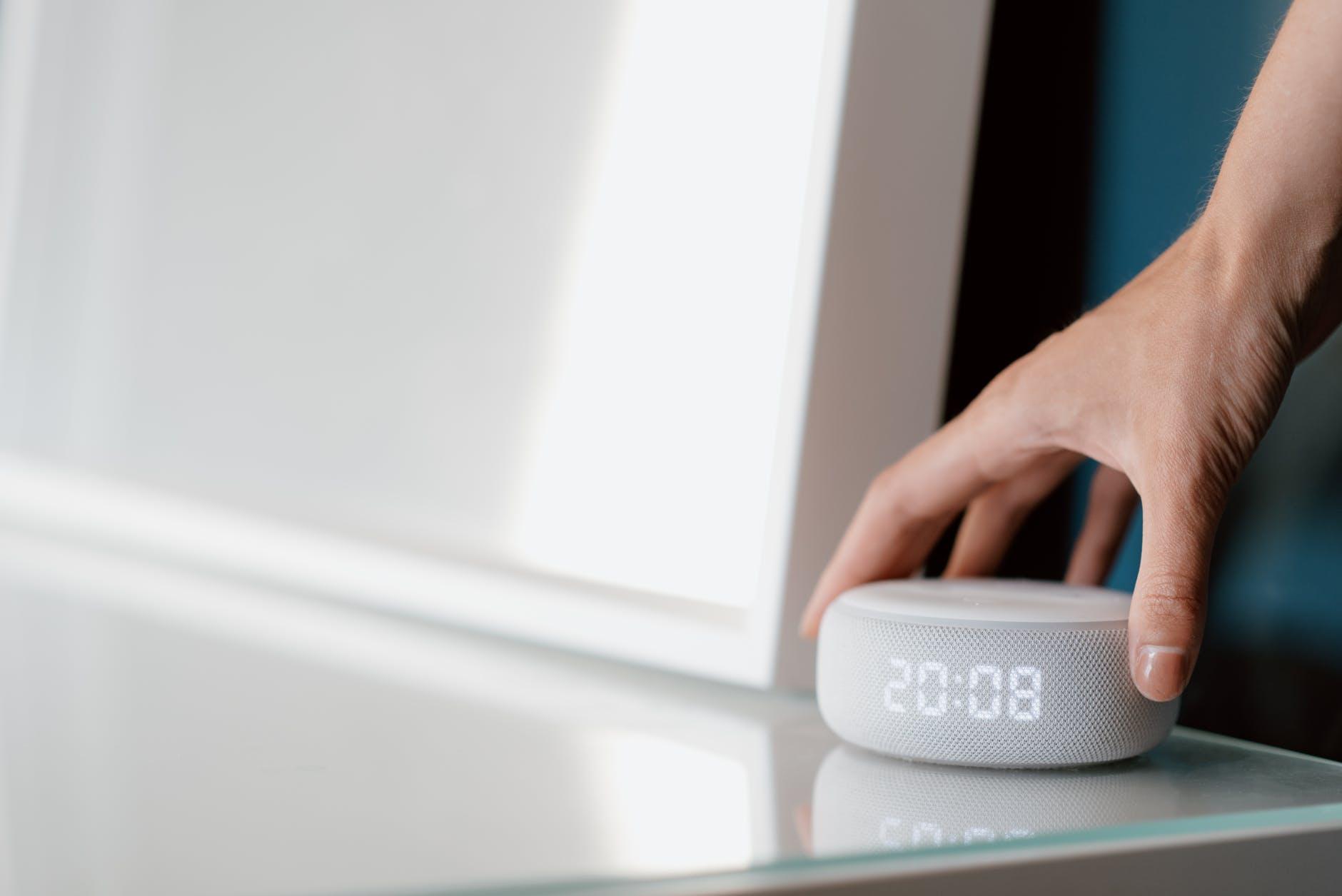ajustando un smart speaker AlexaDot sobre el escritorio de cristal ecosistema interoperable